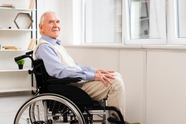 Anziano di vista laterale che si siede sulla sedia a rotelle