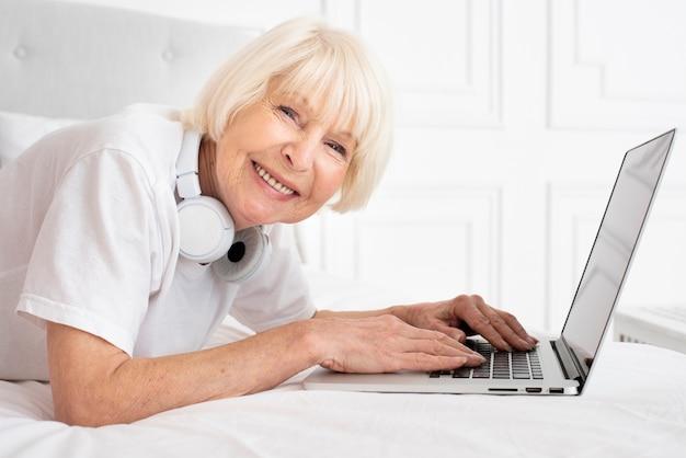 Anziano felice con le cuffie e il computer portatile