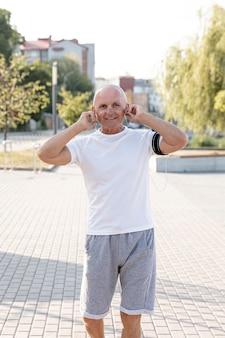 Anziano sorridente che ascolta il colpo medio di musica