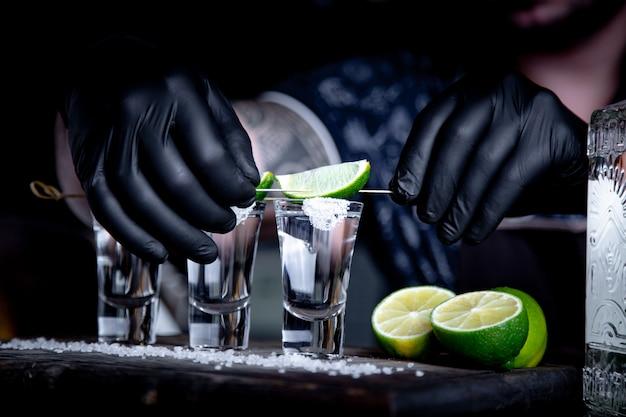 Aperitivo con gli amici al bar, tre bicchieri di alcol con lime e sale per la decorazione. colpi di tequila, fuoco selettivo