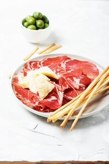 Aperitivo italiano tradizionale con formaggio, prosciutto e grissini, fuoco selettivo