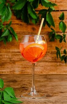 Aperol spritz cocktail con cannuccia su fondo di legno rustico.