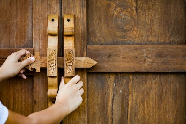 Apertura / chiusura della mano della donna porta in legno in stile vintage