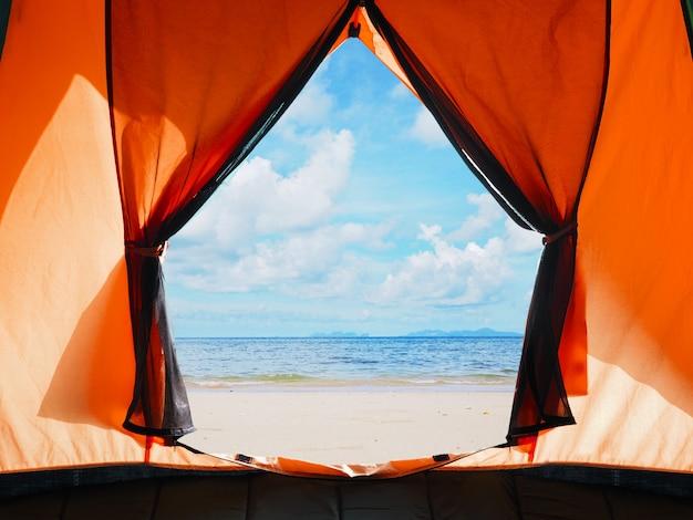 Apertura della porta della tenda arancione campeggio sulla spiaggia estiva