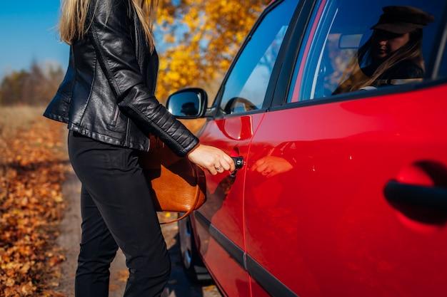Apertura della portiera della macchina. la donna apre l'automobile rossa con la chiave sulla strada di autunno. autista pronto a partire
