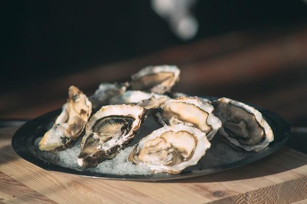 Apertura delle ostriche vuote e piatte. lo chef apre le ostriche nel ristorante.