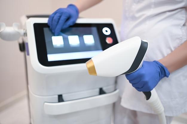 Apparato per la depilazione laser e le mani di un estetista cosmetologo in guanti medici. concetto di epilazione e spa