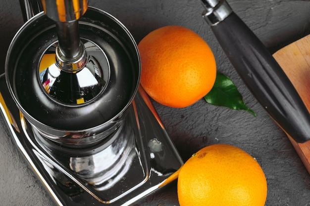 Apparecchiatura arancione degli spremiagrumi sulla fine del tavolo da cucina su