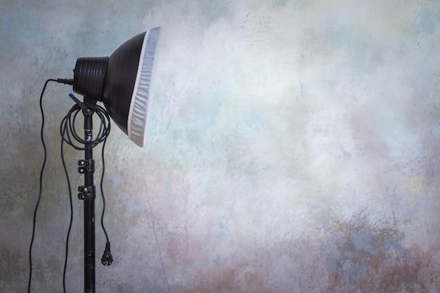 Apparecchiature di illuminazione professionale nello studio fotografico sullo sfondo grigio originale