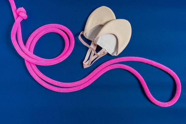 Apparecchiature ritmiche qymnastic. corda per saltare rosa e scarpe relative alla ginnastica isolate sul blu