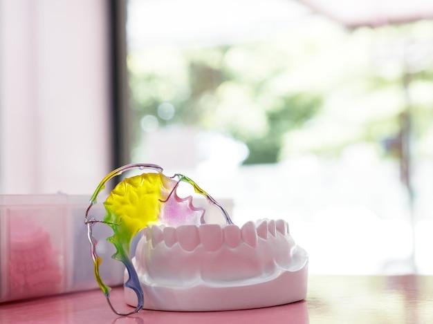 Apparecchio ortodontico di ritenzione dentale sullo sfondo colorato.