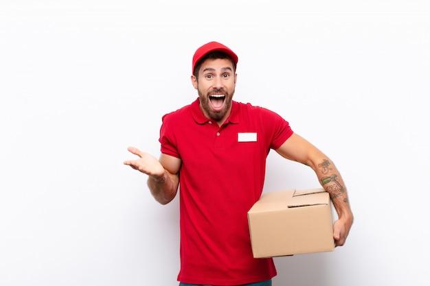 Apparentemente felice ed eccitato, scioccato da una sorpresa inaspettata con entrambe le mani aperte accanto al viso. concetto di consegna