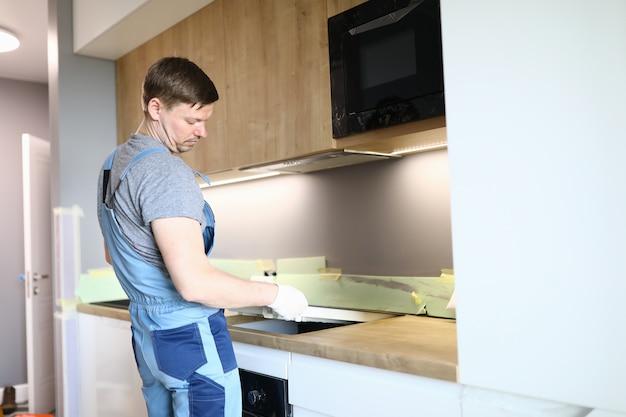 Appartamento elettrico della superficie della cucina di riparazioni dell'uomo