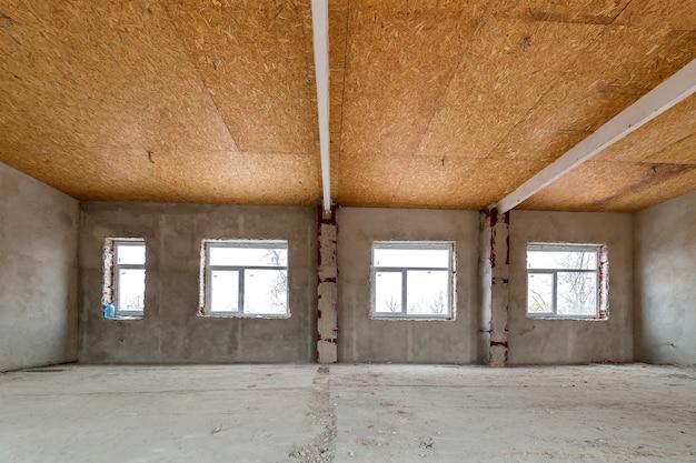 Appartamento incompiuto o casa grande stanza soppalcata in fase di ricostruzione. soffitto in compensato, pareti intonacate, aperture delle finestre, pavimento in cemento. concetto di costruzione e ristrutturazione.