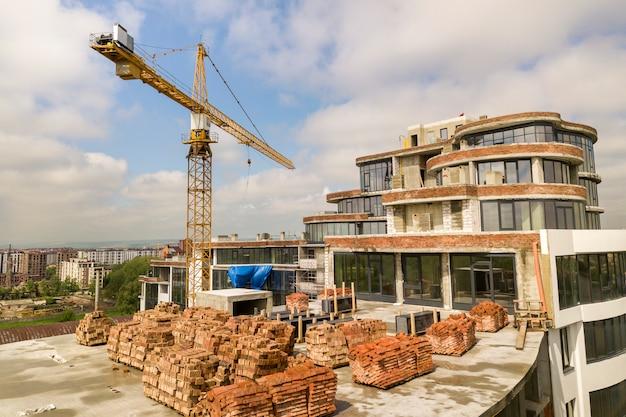 Appartamento o edificio alto in costruzione. pareti in mattoni, finestre in vetro, ponteggi e pilastri di sostegno in cemento. gru a torre sul fondo luminoso dello spazio della copia del cielo blu.
