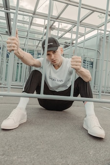 Appassionato di sport in posa dietro la recinzione in ferro allo stadio.