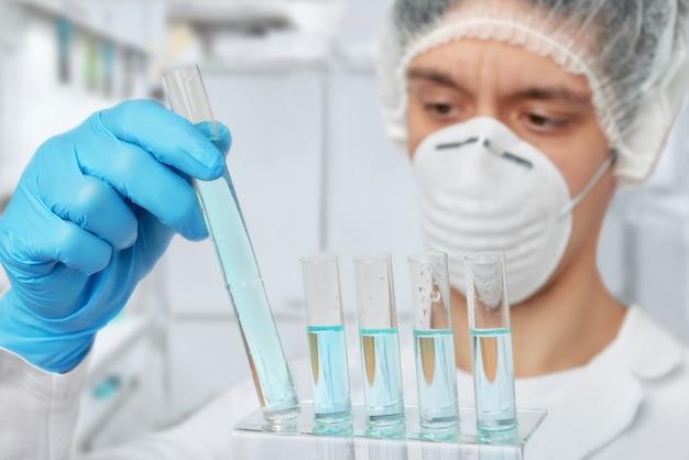 Appassionato scienziato in abbigliamento protettivo con campioni liquidi
