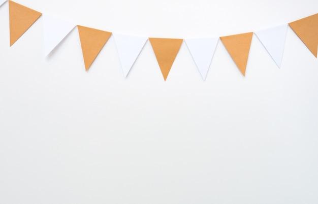 Appendere le bandiere di carta sul fondo bianco della parete, oggetti di arredamento per la festa, il festival, celebrare l'evento