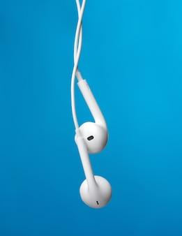 Appendere le cuffie su un cavo bianco, un gadget moderno su sfondo blu