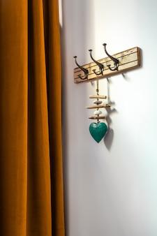 Appendiabiti in legno in stile vintage con cuore decorativo ciano e tenda arancione. ganci su un muro all'ingresso di casa