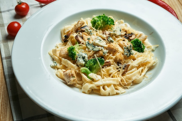 Appetitosa, pasta fatta in casa (tagliatelle) con broccoli, gorgonzola e pollo in un piatto bianco su un tavolo di legno. cucina italiana tradizionale