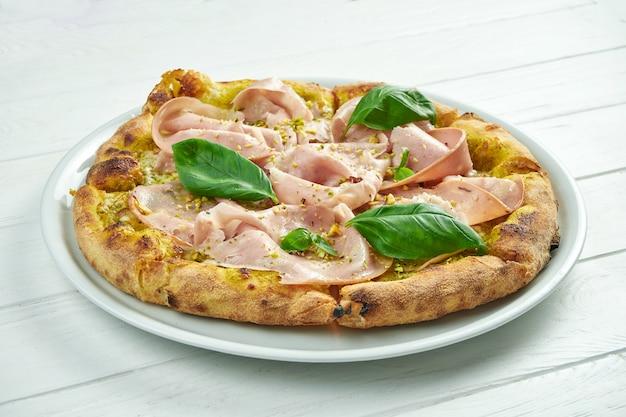 Appetitosa pizza fatta in casa con mortadella, pistacchi, basilico e formaggio fuso su un bianco