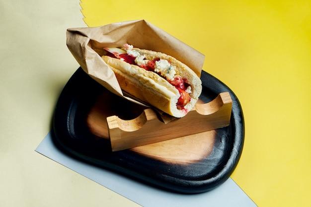 Appetitoso classico hot dog americano con cipolle caramellate, formaggio cheddar, senape e ketchup con contorno di patate su una superficie colorata fast food