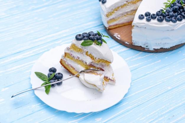 Appetitoso cuscino biscotto biscotto decorato bianco crema mirtilli e supporti di menta sul tavolo rustico blu in legno. torta dolce con pezzo e cucchiaio sul piatto