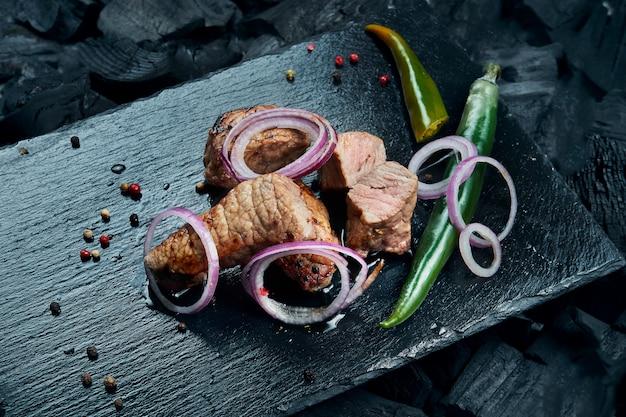 Appetitoso kebab di manzo con spezie e cipolle su un vassoio di ardesia nero su una superficie di carbone. shahlik. chiuda sulla porzione di carne alla griglia