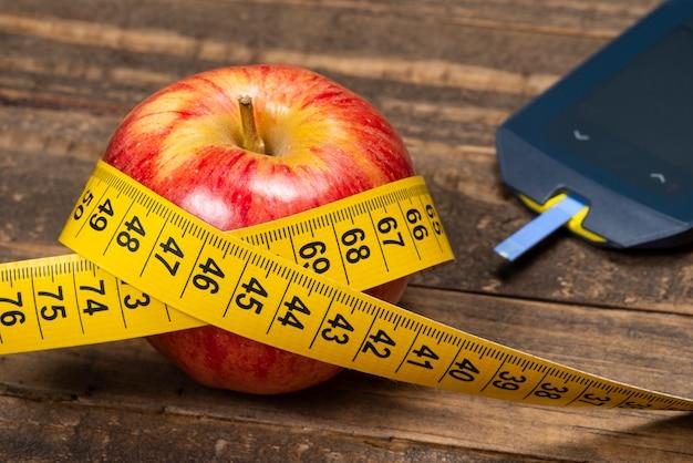 Apple con nastro di misurazione, che simboleggia il sovrappeso