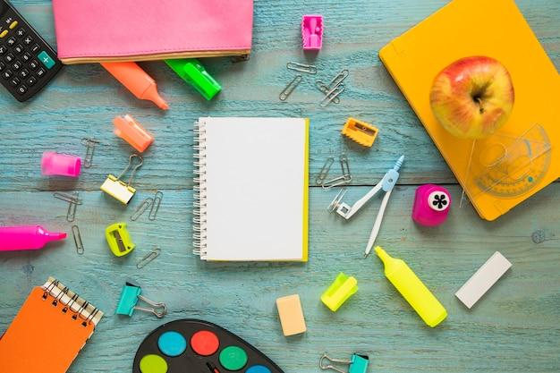 Apple e articoli di cancelleria attorno al notebook