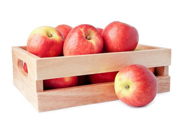 Apple fruttifica nell'isolato della scatola di legno su fondo bianco con il percorso di ritaglio.
