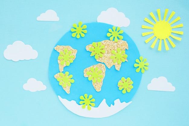 Applicazione cartacea: pianeta terra, continenti, nuvole, sole e virus verdi su sfondo blu. concetto di pandemia di coronavirus