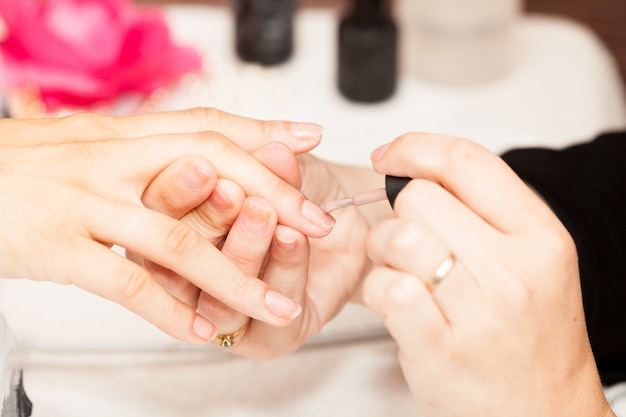Applicazione dello smalto sulle mani di una donna