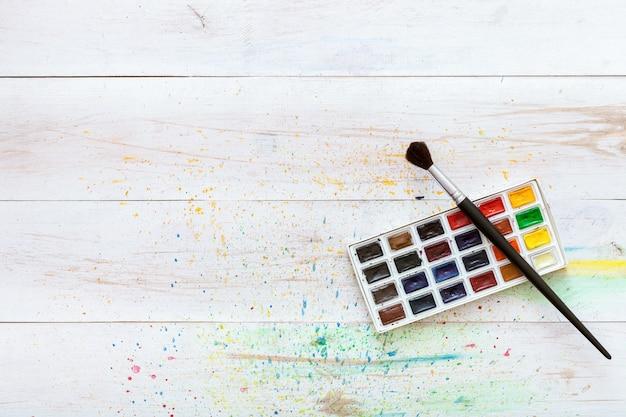 Apprendimento del concetto di pittura, pennello e scatola con acquerelli sul tavolo di legno bianco con spruzzi, sfondo artistico, posto di lavoro di arte creativa per bambini bambini, vista dall'alto con spazio di copia, lay flat