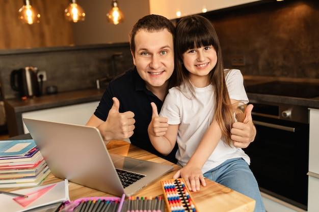 Apprendimento online e unione familiare. studentessa felice e suo padre a casa. formazione a distanza, scuola a casa.