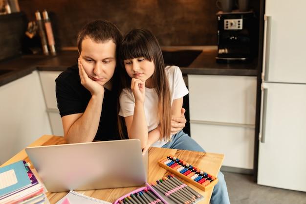 Apprendimento online familiare. studentessa e suo padre a casa, lezione online, videochiamata sul portatile. formazione a distanza, scuola a casa. famiglia unita