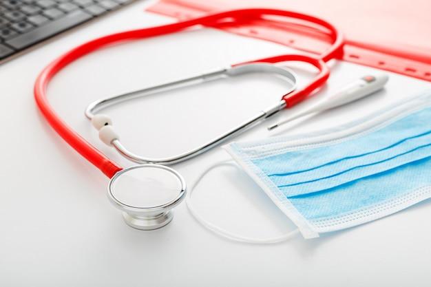Appuntamento dal dottore. termometro, stetoscopio rosso, maschere mediche, maschera di protezione chirurgica, computer sul tavolo bianco in clinica. medicina di medicina di concetto. prevenzione del coronovirus covid-19