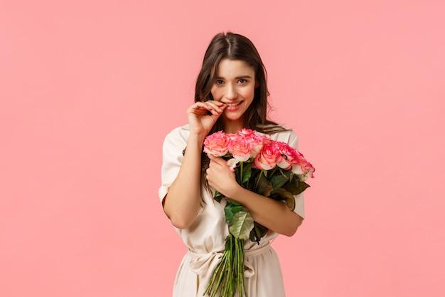 Appuntamento romantico, concetto di bellezza e moda. splendida ragazza bruna in abito, ricevere bellissimi fiori bouquet, rose, dito mordace e flirty, in piedi muro rosa