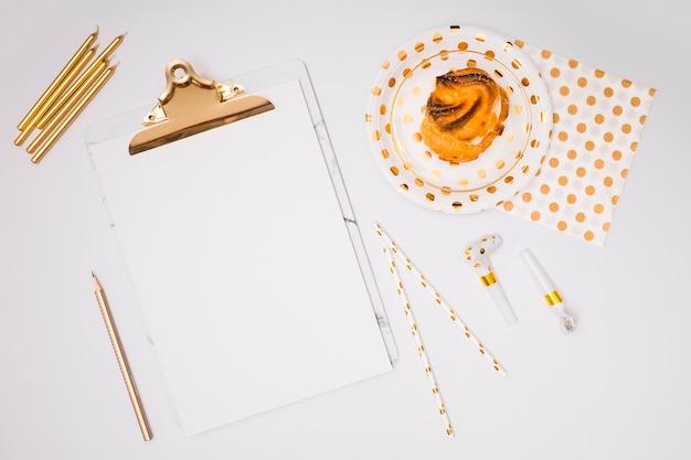 Appunti bianchi mock-up accanto a forniture di compleanno giallo