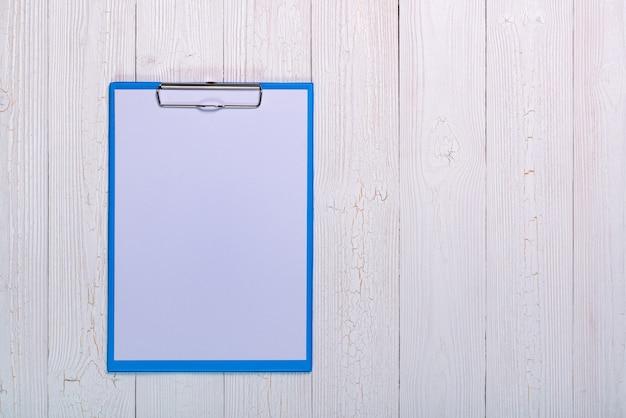 Appunti con foglio di carta bianco bianco su legno