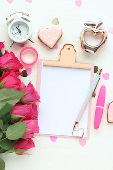 Appunti con foglio di carta bianco, penna, bouquet di rose rosa brillante, sveglia, statuina di mela dorata, cuori di caramella, nastro adesivo e pennarello su un tavolo bianco. layout piatto, vista dall'alto.