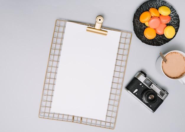 Appunti con macchina fotografica, biscotti e caffè