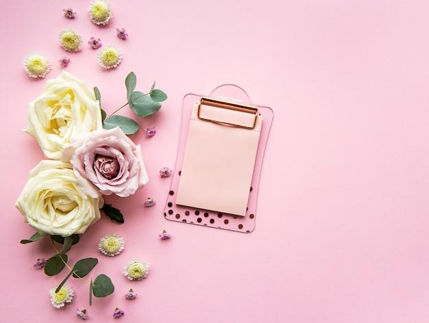 Appunti e fiori su sfondo rosa