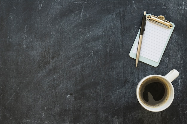 Appunti in miniatura con penna e tazza di caffè sulla lavagna