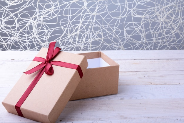 Apra i contenitori di regalo con l'arco su fondo di legno. decorazione natalizia
