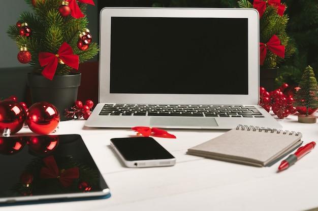 Apra il blocco note e il computer sulla tavola con la decorazione di natale