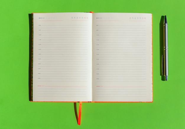 Apra il blocco note vuoto e la penna grigia su fondo verde