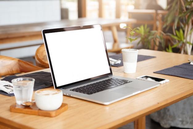 Apra il computer portatile con lo schermo bianco in bianco sulla tabella