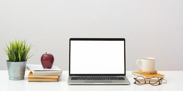 Apra il computer portatile dello schermo in bianco con gli articoli per ufficio e le decorazioni